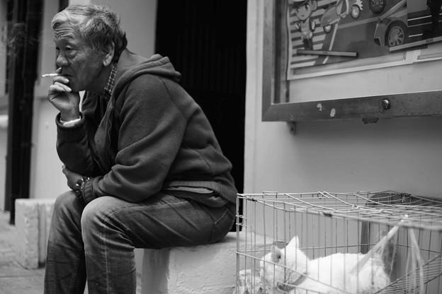 煙草を吸う男と猫