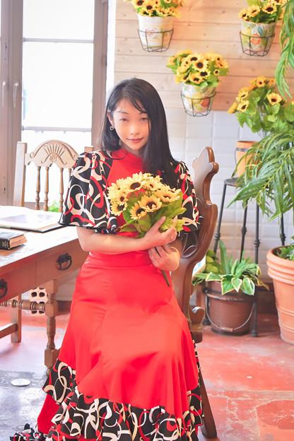 Una niña con girasoles y ropa roja