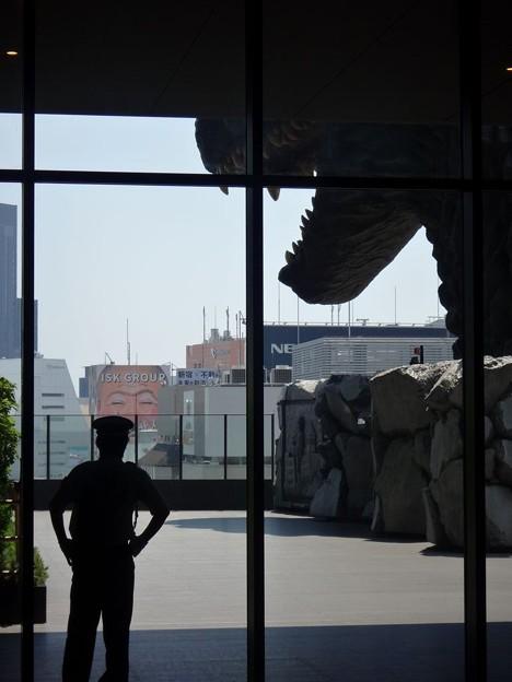 写真: 警備員の後ろにゴジラがいる