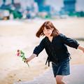 写真: 花を持って波と遊ぶ