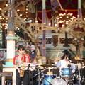 写真: 回転木馬前の女性楽団